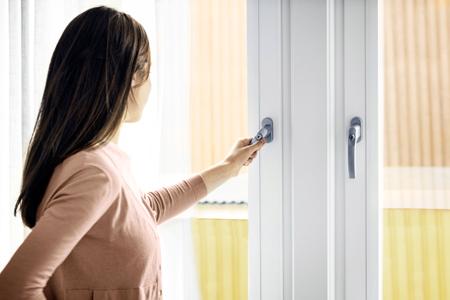 kvinna öppnar PVC fönster