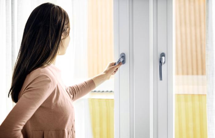 tjej öppnar ett pvc fönster